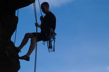 Silhouette of male rock climber hanging from ropes.