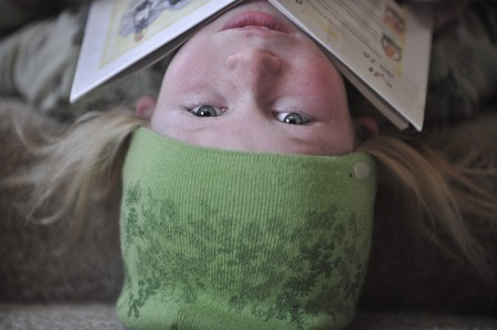 Little girl upside down, with a book resting on her chin. photo