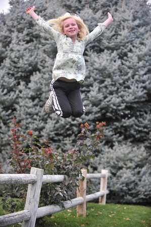 outspread: Young girl jumping from a fence with arms outspread