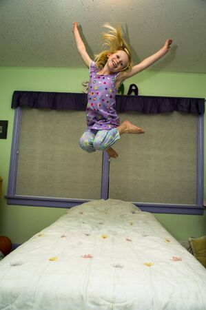 frolicking: Young girl jumping on a bed in a bedroom with green walls. Stock Photo