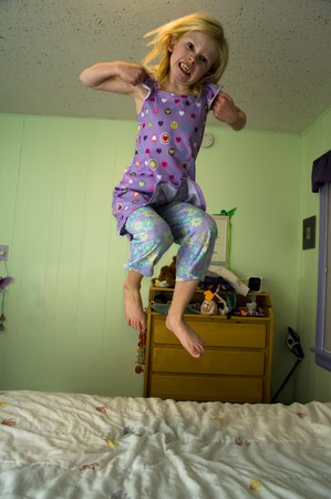 Angry young girl jumping on a bed in a bedroom with green walls.