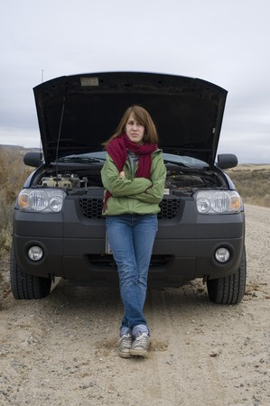 Teenage girl standing in front of her broken-down car, with the hood up. photo