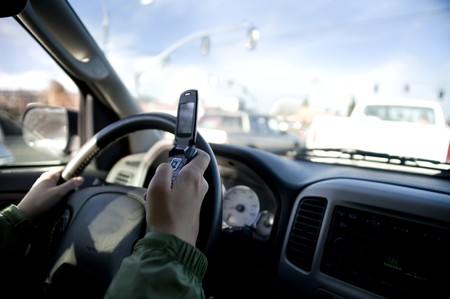 Person texting on a cell phone while driving a car. Stock Photo