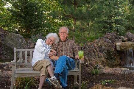 water feature: Senior man and woman sitting on a bench by a man-made pond and waterfall