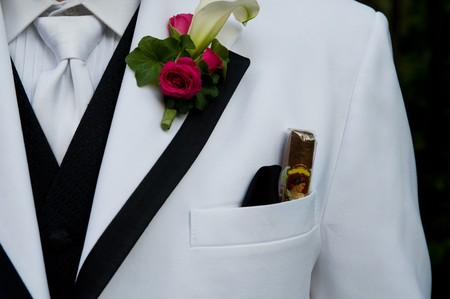 breast pocket: Closeup of a mans tuxedo. A cigar is tucked in the breast pocket.