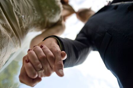 Couple holding hands and kissing. Focus is on the hands.