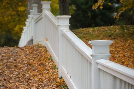 autumn colour: Old white picket fence in an autumn landscape. Stock Photo