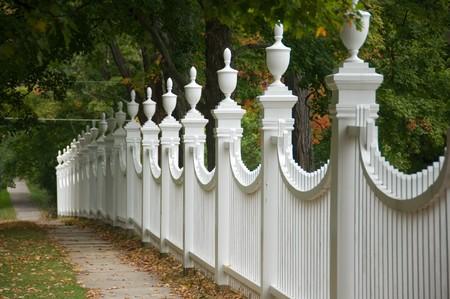 Old white picket fence in an autumn landscape. Standard-Bild