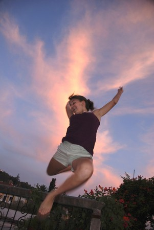 Teenage caucasian girl leaping, with a sunset in the background. photo