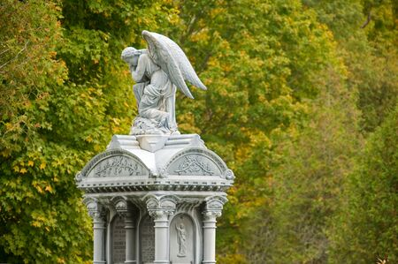 Statue of an angel in a cemetery, with out-of-focus trees in the background. photo