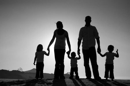 bw: Beautiful silhouette of a family, with the sun setting behind them, standing on a hill.