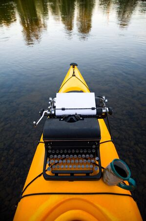 Kayak with a typewriter and a coffee cup on it.