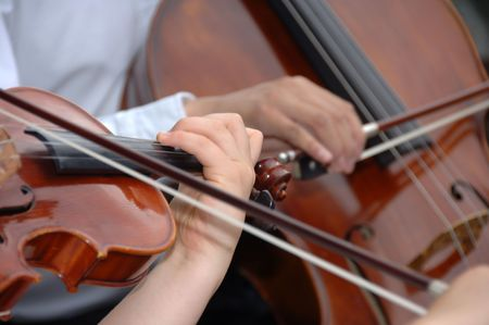 cellist: Violinist and cellist playing their instruments with bows