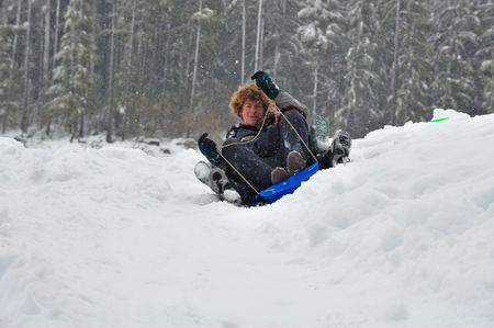 Teenagers sledding in the snow on a saucer. Winter fun. photo