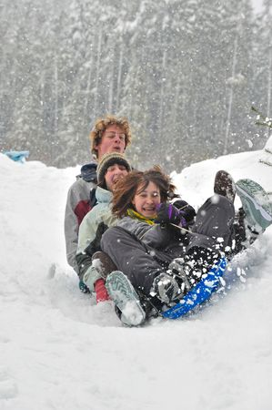 Teenagers sledding in the snow on a saucer. Winter fun. Stock Photo
