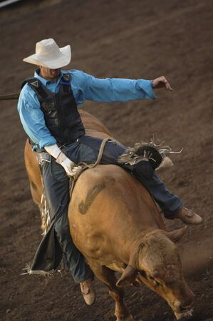 Cowboy riding a horse at a rodeo.