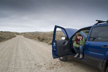 Teenage girl talking on a cell phone, trying to get help with her broken car. photo