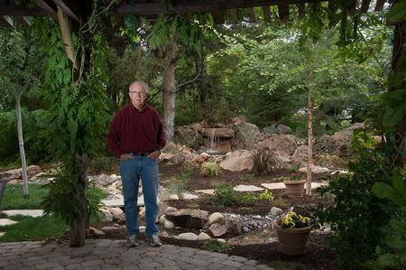 water feature: Senior man standing by a man-made pond and waterfall