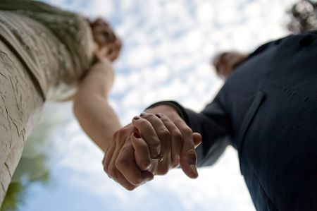 Couple holding hands. Focus is on the hands.