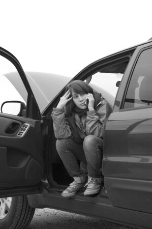 Teenage girl talking on a cell phone, trying to get help with her broken car.
