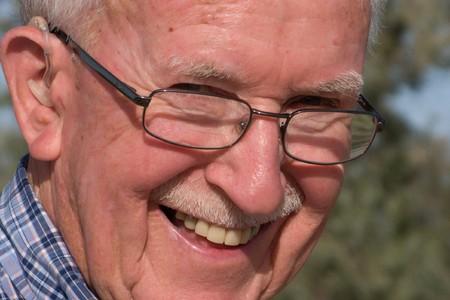 Happy senior man with a hearing aid