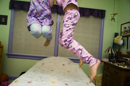 frolicking: Legs of two girls jumping on a bed