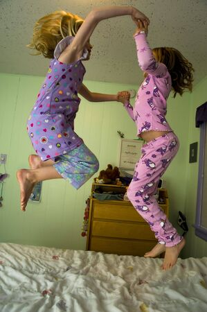 frolicking: Two girls jumping on a bed in a bedroom with green walls.