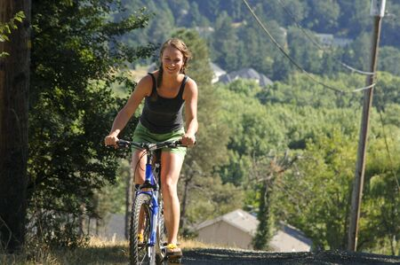 Pretty caucasian teenage girl riding a bicycle.