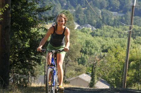 riding bike: Pretty caucasico ragazza in sella a una bicicletta. Archivio Fotografico