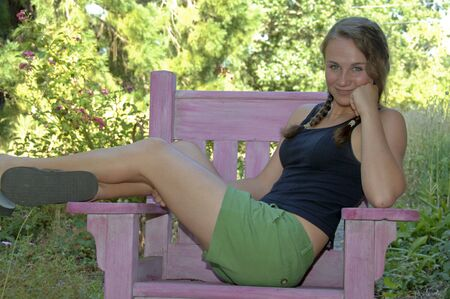 Pretty teenage girl stretched out in a pink wooden chair photo