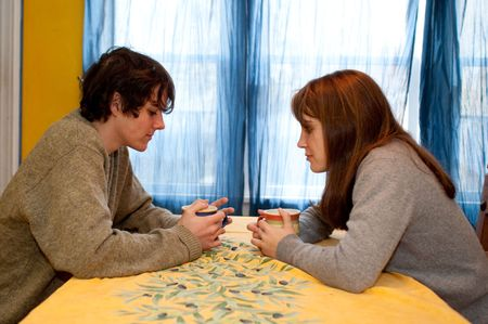 Teen couple talking over coffee or tea, at a yellow table. Stock Photo