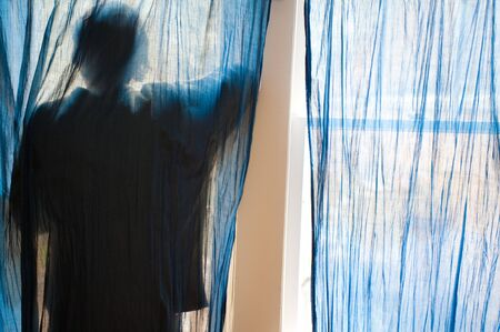 Young man looking out a window behind blue curtains. photo
