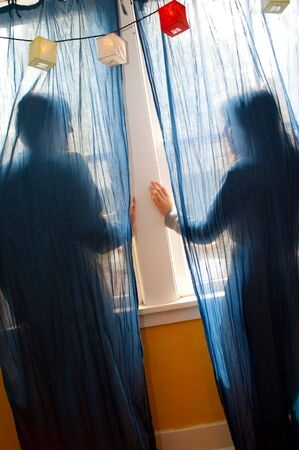 Young couple looking out a window behind blue curtains. photo