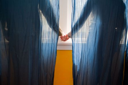 Young couple holding hands behind blue curtains. photo
