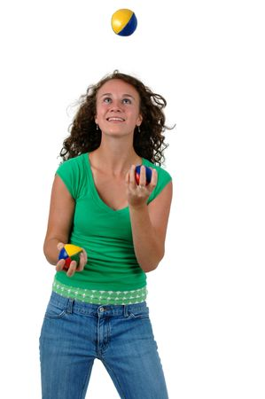 Isolated portrait of a teenage girl juggling three balls.
