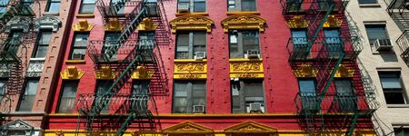 Brightly painted red and yellow building in Chinatown in New York City, in panoramic format.