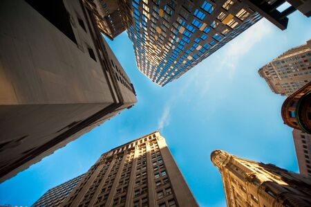 Looking up toward the sky among tall skyscrapers.