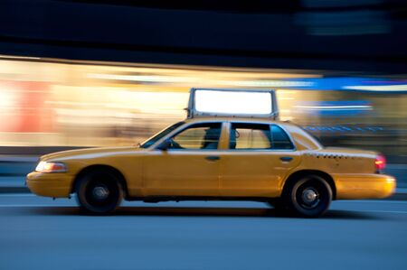 Taxi on an urban street at night, blurred as it races down the street. Use the empty copyspace on top to place your message. Stock Photo