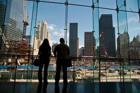 People in silhouette looking at construction at the Trade Towers site.