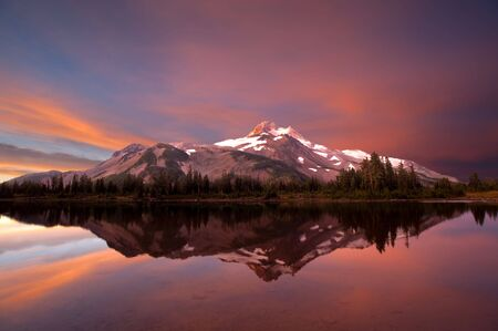 Mt. Jefferson in Oregons Cascade Range, reflected in a lake at sunrise