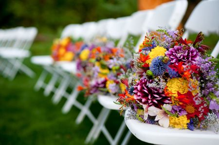 Bouquets of the bridesmaids lined up on chairs