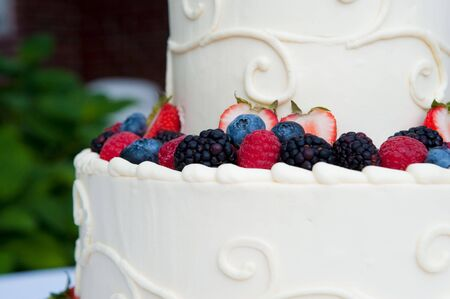 Multi-layered white wedding cake with fruit Stock Photo