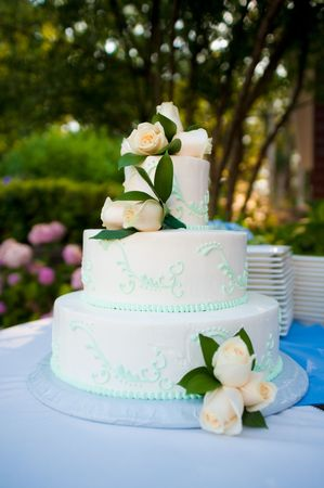 Multi-layered white wedding cake with roses Standard-Bild