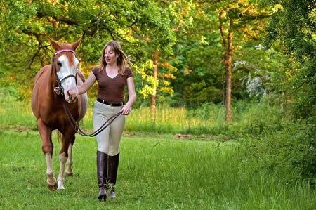 horse blonde: Woman leading a horse through a forest