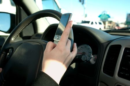 Hand of a girl texting with cell phone, hand on steering wheel