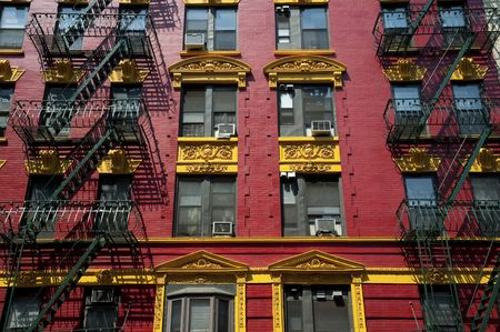 apartment: Brightly painted red and yellow building in Chinatown in New York City. Stock Photo