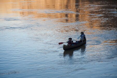 Mother and daughter canoeing on a calm blue river photo
