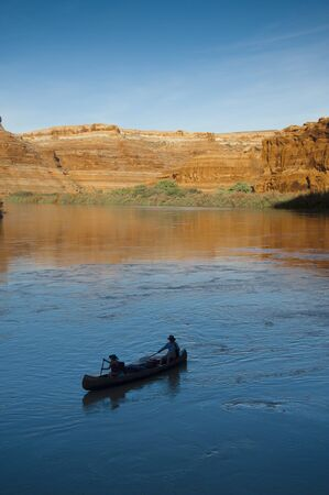 Mother and daughter canoeing on a calm blue river in the desert photo