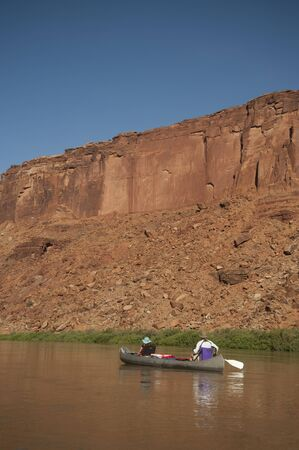 Mother and daughter canoeing on a calm blue river in the desert country of Utah photo