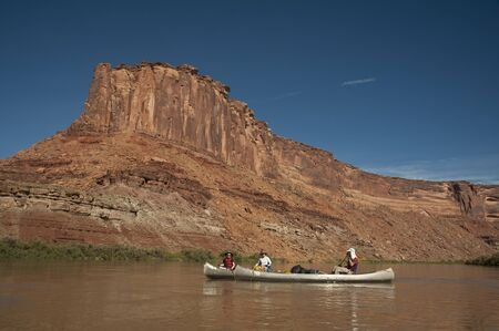Family canoeing down a desert river in the canyons of Utah photo